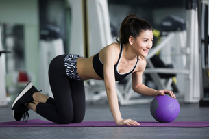 Young woman exercising with medicine ball at gymの写真素材 [FYI02857396]