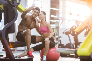 Young couple taking self portrait in the gymの写真素材 [FYI02857398]