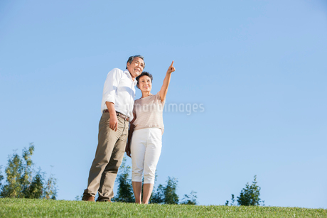 Happy mature couple looking at view in a parkの写真素材 [FYI02857404]