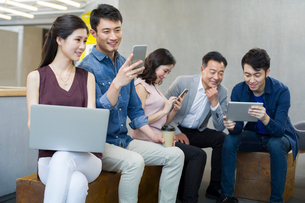 Business people using portable devices in officeの写真素材 [FYI02857406]