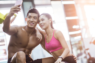 Young couple taking self portrait in the gymの写真素材 [FYI02857409]