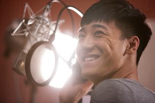Young man singing in recording studioの写真素材 [FYI02857413]