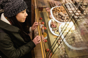 Woman looking at desserts at dessert counterの写真素材 [FYI02857436]