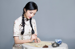 Young beautiful woman in traditional cheongsam practicing calligraphyの写真素材 [FYI02857448]