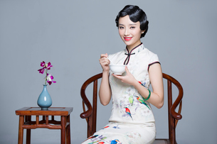 Young beautiful woman in traditional cheongsam eating porridgeの写真素材 [FYI02857450]
