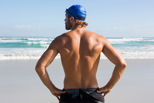 Rear view of shirtless athlete standing at beachの写真素材 [FYI02857458]