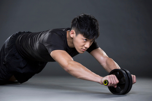Young man exercising with Ab wheelの写真素材 [FYI02857459]