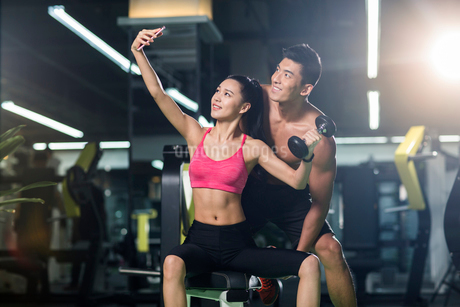 Young couple taking self portrait in the gymの写真素材 [FYI02857463]