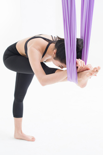 Young Chinese woman practicing aerial yogaの写真素材 [FYI02857471]