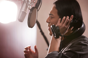 Young man singing in recording studioの写真素材 [FYI02857474]