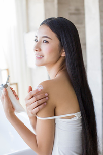 Young woman applying moisturizer to shoulderの写真素材 [FYI02857475]