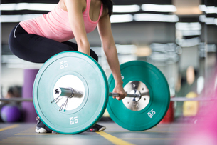 Young woman lifting barbell at gymの写真素材 [FYI02857480]
