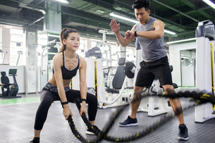 Young woman working with trainer at gymの写真素材 [FYI02857484]