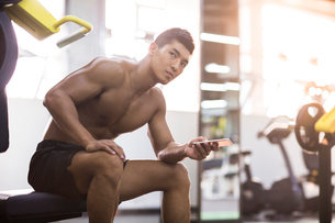 Young man using smart phone in gymの写真素材 [FYI02857487]