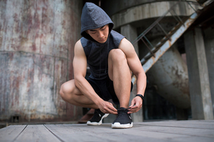 Young Chinese man tying shoe laceの写真素材 [FYI02857489]