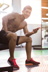 Young man using smart phone in gymの写真素材 [FYI02857499]