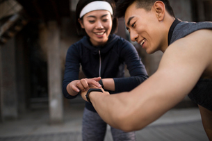 Young Chinese couple checking smart watch after runningの写真素材 [FYI02857522]