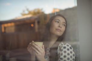 Woman having cup of coffee near windowの写真素材 [FYI02857525]