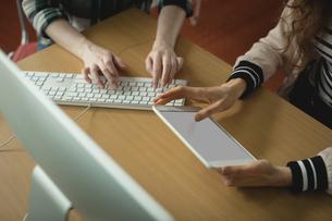 Women using computer and digital tablet in collegeの写真素材 [FYI02857531]