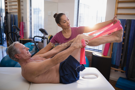 Female therapist looking at male patient pulling resistance band while lying on bedの写真素材 [FYI02857547]