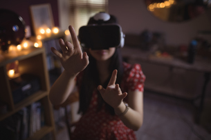 Woman gesturing while using virtual reality headsetの写真素材 [FYI02857550]