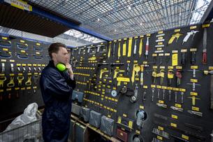 Male aircraft maintenance engineer examining various work toolの写真素材 [FYI02857564]