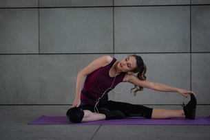 Woman performing stretching exercise in fitness studioの写真素材 [FYI02857565]