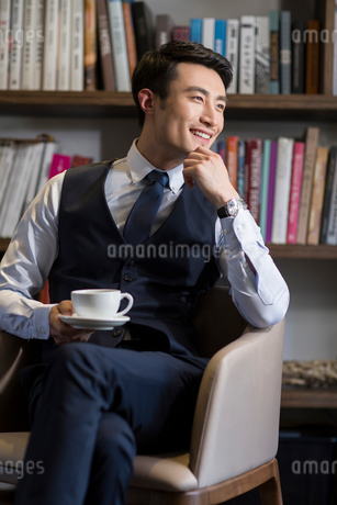 Young businessman drinking coffee in his studyの写真素材 [FYI02857567]