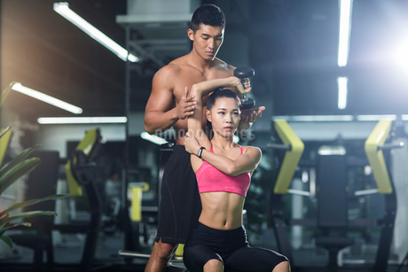 Young woman working with trainer at gymの写真素材 [FYI02857568]