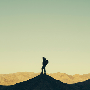 A male hiker on a hilltop in Death Valley national park.の写真素材 [FYI02857570]