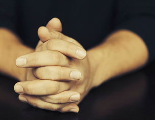 The clasped hands of a man wearing dark coloured clothes.の写真素材 [FYI02857594]