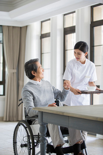 Nursing assistant taking care of senior man in wheel chairの写真素材 [FYI02857600]