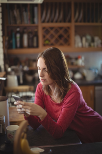 Woman using mobile phone in kitchenの写真素材 [FYI02857603]