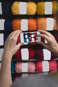 Woman taking photo of yarn with mobile phoneの写真素材 [FYI02857634]