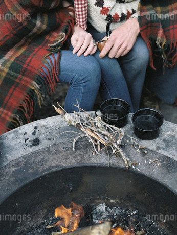 Detail of couple sitting by a fire pit.の写真素材 [FYI02857668]
