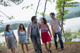 A group of people enjoying a leisurely walk by a lake.の写真素材 [FYI02857681]