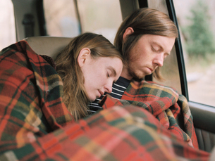 A couple taking a nap in their car, covered by a blanket.の写真素材 [FYI02857683]