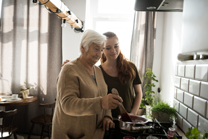 Grandmother and grand daughter cooking in the kitchenの写真素材 [FYI02857707]