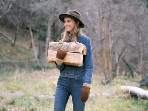 Young blond woman wearing a hat, carrying firewood.の写真素材 [FYI02857710]