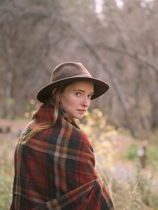 Young blond woman wearing a hat, wrapped in a blanket.の写真素材 [FYI02857715]