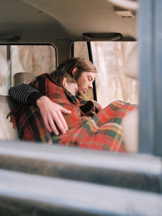 A couple taking a nap in their car, covered by a blanket.の写真素材 [FYI02857725]