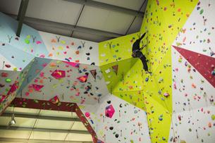 Man practicing rock climbing on artificial climbing wallの写真素材 [FYI02857726]