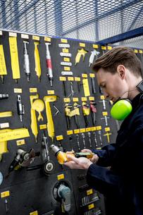 Male aircraft maintenance engineer examining various work toolの写真素材 [FYI02857729]