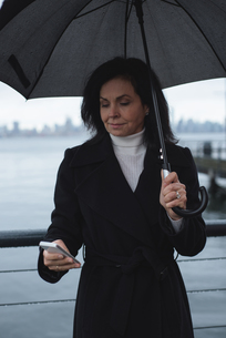 Woman using phone while holding umbrella by riverの写真素材 [FYI02857736]