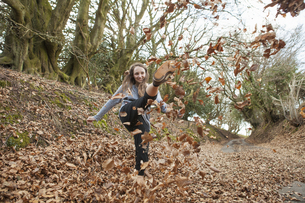 Young woman playing in fallen leaves, kicking them in the air.の写真素材 [FYI02857747]