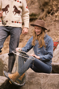 Young couple in a forest, fishing in a river, smiling woman holding a fish in a net.の写真素材 [FYI02857748]