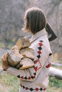 Young blond man carrying firewood.の写真素材 [FYI02857760]