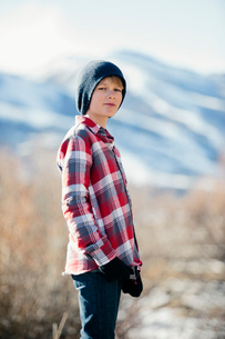 A boy with a woolly hat and checked shirt standing in open countryside in winter.の写真素材 [FYI02857764]