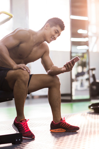 Young man using smart phone in gymの写真素材 [FYI02857777]