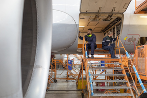 Aircraft maintenance engineers working over an aircraftの写真素材 [FYI02857792]